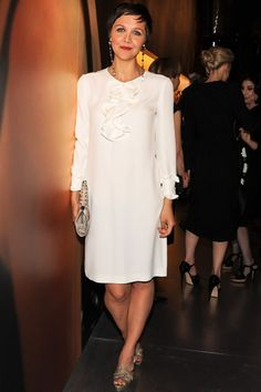 Maggie Gyllenhaal arrived in a white ruffle-front Prada dress with metallic sandals.