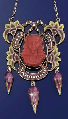 An Art Nouveau silver and enamel pendent necklace The openwork panel with pliqué a jour enamel lotus flower decoration surrounding an imitation jasper pharaoh head, suspending three enamelled flowerbud drops, to oval-link backchain with white and purple enamel candy-twist bar intervals, circa 1900.