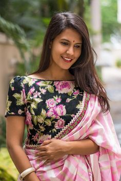 A smart floral boatneck with a slight puff on the sleeves reminiscent of the days of yore! The rounded V back and the pom pom edge detailing make this blouse all the more special. Pair it with a dreamy pastel saree or any saree with white detailing and float on that cloud!