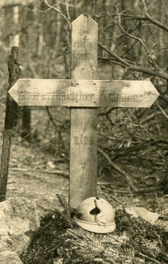 """Detail - French Fighter's Grave with His Shell-Pierced Helmet. AGerman made PC of a grave made by Germans in honor of an unknown French soldier. """"Here rests in peace a French Fighter - August 1, 1916"""" reads the inscription and they laid his shrapnel torn helmet on the grave."""