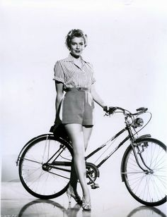 Deborah Kerr stands by a bike.