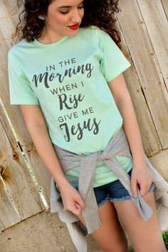 "Our In The Morning Tee features a mint super-soft tee with the phrase ""In The Morning When I Rise Give Me Jesus"" printed on the front in gray. Made of 100% Cotton. Model is a size 2 and is wearing a s"