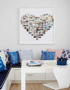 Creative home office features a Parsons desk from West Elm sat on blonde wood floors and surrounded a single West Elm Scoop Back Chair and an L-shaped built in bench with pull out drawers positioned under navy blue seat cushions accented with white piping and an assortment of blue and red accent pillows.