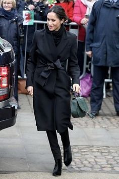 Meghan Markle wearing Stella McCartney Tie Detail Coat, Theory Wool Off the Shoulder Jacket, Demellier London the Mini Venice Bag in Forest Green, Tabitha Simmons Kiki Boots and Hiut Denim Dina Jeans