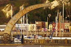 Victorian Fairbairn Crane at Sunrise, Wellington Dock, Dover Marina, Kent, England, UK. A swan-neck tubular crane located on Esplanade Quay with Snargate Street and White Cliffs of Dover (Western Heights) in the background. Built in 1868, this is a later example of a revolutionary design shown at the 1851 Crystal Palace Great Exhibition of London. English Heritage Listed Building. Industrial Archaeology, Archeology, History. Engineering, Machine. See: http://www.panoramio.com/photo/50288025