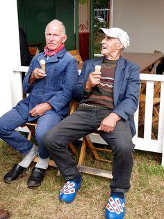 de Boer op Friese klompen eet een lekker ijsje. Oudehorne. Friesland: