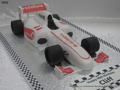 F1 Racing Car Cake. Bracknell to Brands...... Large silver shimmered formula one racing car cake decorated with typical livery, logos and trimmings. Large chequered message plaque and age endorsed tail to make it personal. Any team any livery