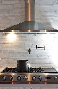 hood, faucet, stove, with backsplash behind hood.