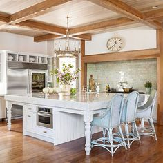 Country French Flair   This kitchen's range takes center stage with the help of a light green backsplash. The glossy tiles complement the room's exposed wood paneling and expansive marble island.