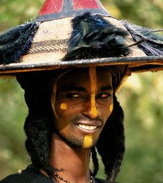 "Wodaabe Man, Niger    ""Inyi casts a seductive glance at the young nomad girls attending the Geerewol festival [where Wodaabe men compete in tests of dance and beauty.]"" Photographers Carol Beckwith  Angela Fisher"