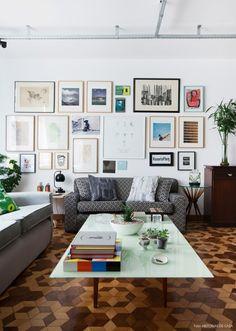Sala de estar com mistura de móveis vintage e contemporâneos, piso de tacos e parede com muitos quadros.
