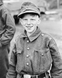 A cheerful young German boy soldier captured by the 11th Armored Division, Third US Army, near Kulmbach, Germany, 15 April 1945. Although wearing a German Army uniform, he had not been issued arms. He was one of a group being marched to the Czechoslovak border for unknown reasons. Such kids in uniform were usually turned over to the Red Cross.
