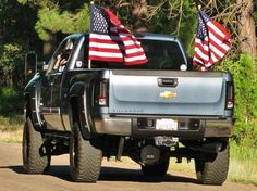 lifted blue Silverado US Chevrolet truck with old Betsy US flag