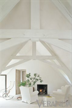 Axel Vervoordt . white painted beams . minimalistic fireplace . door COLOR FOR ENTRY SIDE OF DR DOOR