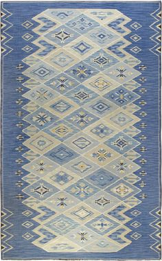 A Swedish Flat Weave Rug Designed by Sofia Widen with a play on overlapping diamond motifs that create a modern geometric design with a casual folk art flair. Linear half diamonds create a border on the sides. Multiple shades of blue with Ivory, Tan and Yellow . Signed SW lower left.