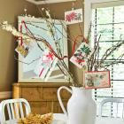"""Shabby Chic/Cottage/Vintage looking: Show off Christmas cards on a centerpiece """"tree"""" made with twigs from the yard. Arrange twigs in a pitcher or vase, and clip or tie cards to twig ends. For an added burst of holiday color, weave a red ribbon or piece of rickrack through the display."""