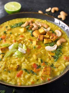 Thai Coconut Curry Stew - a warming, comfort food meal that's perfectly spiced with savory curry and Thai flavors like ginger, lemongrass, and kaffir leaves. Pan-fried, curry-rubbed tofu and rice round out this filling, satisfying stew. Recipe at SoupAddict.com | vegetarian stew | vegetarian stew recipe | healthy stew | vegan stew | gluten-free | coconut curry soup | thai stew | tofu | food in bowls