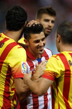 David Villa of Atletico de Madrid is embraced by his ex-teammates of FC Barcelona prior to start the Spanish Super Cup first leg match between Club Atletico de Madrid and FC Barcelona at Vicente Calderon Stadium on August 21, 2013 in Madrid, Spain.