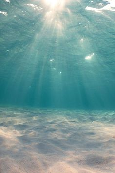 Underwater crystal clear water on a white sandy beach with sunshine peeping through.