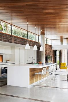 ...this open-plan kitchen/living room area has spun traditional interior design on its head with a wooden roof and shiny white flooring. Surprisingly, this seems to work!