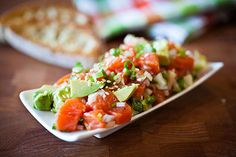 Salmon Tartar with Avocado:1 lb. raw salmon; 2 scallions, thinly sliced;1 small shallot, minced; 1 jalapeno, minced; juice of 1/2 lemon; zest of 1/2 a lemon; 1/2 small cucumber, minced; 1 tsp olive oil; pinch salt and pepper; 1/2 an avocado, cubed; sesame seeds, to garnish
