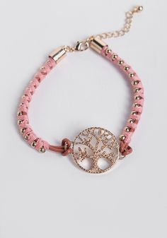 This lovely bracelet features a faux leather cord wrapped with light-pink thread and gold-toned beads.