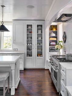 Cantley & Company hides a recessed hood with a sheet-rock arch, adds nice mid-level lighting with the wall sconces and maximizes the wall space with inset shelving for a fully functional and pleasing kitchen!