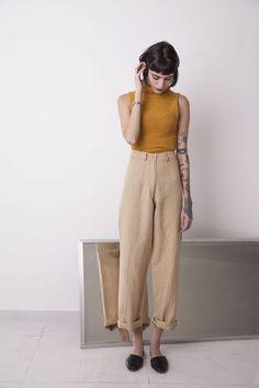 Tons terrosos: 37 looks para você apostar nessa trend. Regata de gola alta amarela, calça de alfaiataria com barra dobrada, cáqui, mule preto