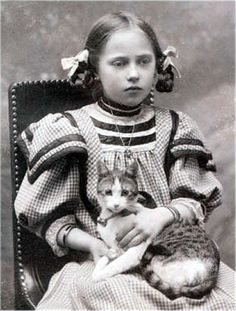 Girl in check dress, with tabby and white cat.