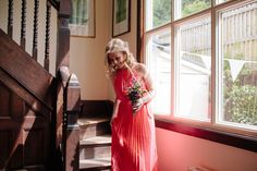 Bridesmaid wears a coral gown  | Photography by http://lmweddings.co.uk/