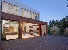 grande baie vitrée coulissante ultra moderne qui sépare la terrasse en bois composite du salon contemporain