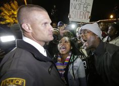 Protesters yell in the face of a St. Louis County police officer during a protest at the Ferguson, Mo., police headquarters Friday, Oct. 10, 2014, in Ferguson.  (AP Photo/Charles Rex Arbogast)
