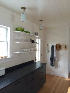 Dark gray under the counter kitchen cabinets and open shelves above, Shaker pegs with hats and clothing, Goode Kitchen, Amagansett | Remodelista