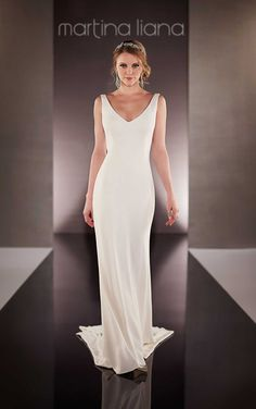 Simple, yet stunning, this Bellagio crepe sheath wedding dress from the Martina Liana bridal gown collection offers a sexy plunging neckline and back. Crepe-covered buttons accent the wedding gowns chapel train.