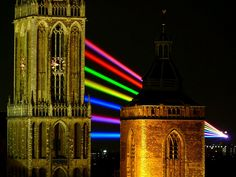 """Global Rainbow"" by Yvette Mattern is a massive scale outdoor light projection in which seven high power lasers project a rainbow light beam for up to five miles."