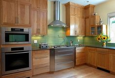 Lovely green tile is the star of this kitchen with everything else light & neutral. Also love the Miele steam oven atop the single wall oven. So functional.