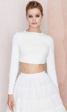 The Stunner Crop Top comes in ivory and features long sleeves, a split back, seam detailing, and button closures at back.