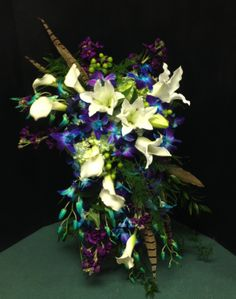 Busch Wedding. 9-30-16 Designed By Mariah Smet Haentze Floral Co  Brides Bouquet featuring Blue Bomb orchids and Pheasant feathers.