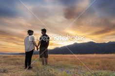 Couple walking hand in hand enjoying the sunset on the last day of summer