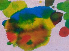 Rode, gele en blauwe ecoline met rietje druppelen op handdoekjes papier.