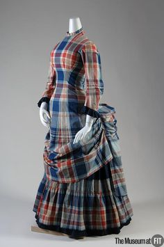 """c. 1880. This two-piece dress features the plaid fabric known as """"madras"""" which originated in the Indian town of Madras, on the Bay of Bengal. Like other Indian printed cottons, it was widely imitated in the West."""