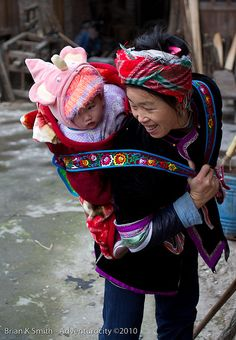 A minority woman carries her bundled up son on her back in a brightly-emroidered baby carrier.