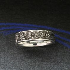 The RIVER RUN Wedding BAND ,with Pine Trees and Flowing Water, in Sterling Silver. $140.00, via Etsy. (BandScapes)