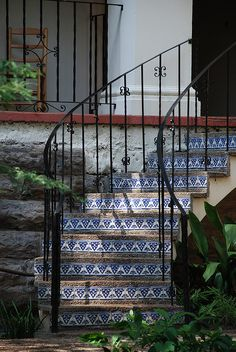Graceful, exterior curved staircase with Spanish tile risers & iron railing.