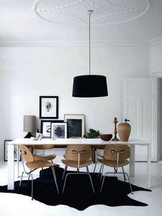 salle à manger blanche avec une déco scandinave en noir et chaises en bois et métal autour de la table blanche