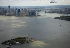 The space shuttle Enterprise, mounted atop a NASA 747 Shuttle Carrier Aircraft, flies near the Statue of Liberty and the Manhattan skyline, on April 27, 2012.