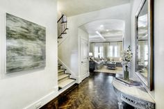 French foyer features whitewashed silver leaf mirror over demi-lune console table atop wood herringbone floor.