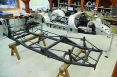 Photo Courtesy: David LaChance The first completed replica chassis, partially covered in new hand-hammered aluminum bodywork, rests next to the chassis of a genuine Porsche 550 Spyder, the 86th of 90 built.