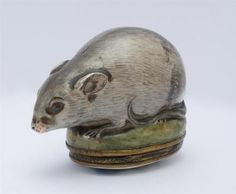 ENGLISH METAL-MOUNTED ENAMEL MOUSE-FORM SNUFF BOX The mouse sitting atop the hinged oval top with floral decoration opening to a welled interior. 2 1/4 x 3 x 1 3/4 in.