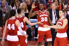 Frank Kaminsky, left, Bronson Koenig, Vitto Brown and the Wisconsin Badgers high five at the end of the 1st half  vs Kentucky at Final Four in Indianapolis